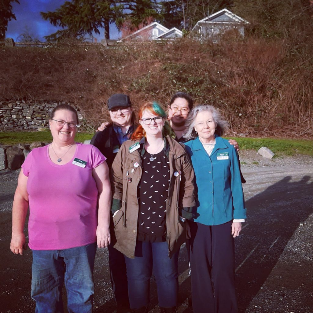 Group photo of the Upper Skagit Library employees smiling in a parking lot with bushes in the background.