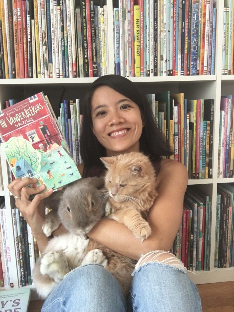 Photo of Karina Yan Glaser sitting in front of a bookshelf holding a book, a large grey bunny, and an orange cat. She is smiling.