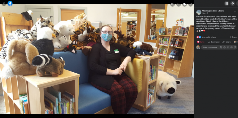 Screenshot of a Facebook post by the Washington State Library, with new library Director Erica Brown sitting on an oversize chair with built-in bookshelves and a dozen stuffed animals surrounding her.